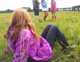Girl sitting in grass at festival